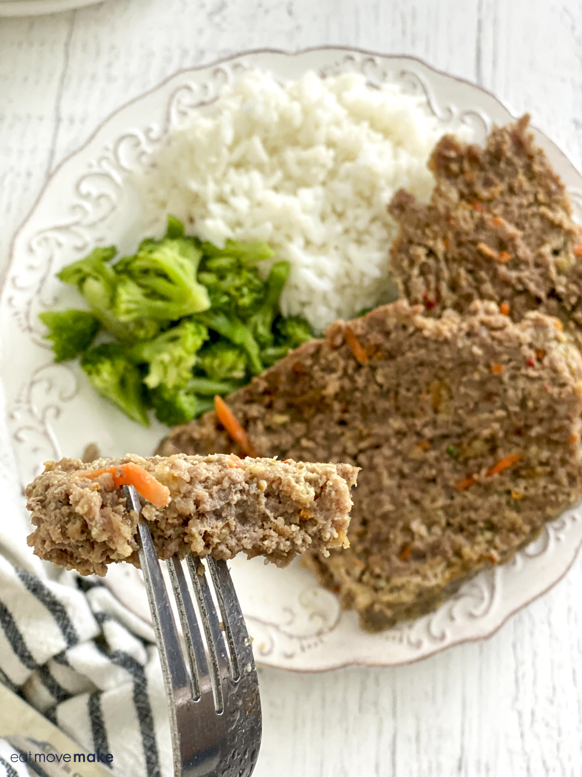 forkful of meatloaf with two slices of meatloaf, broccoli and rice on white plate on white table