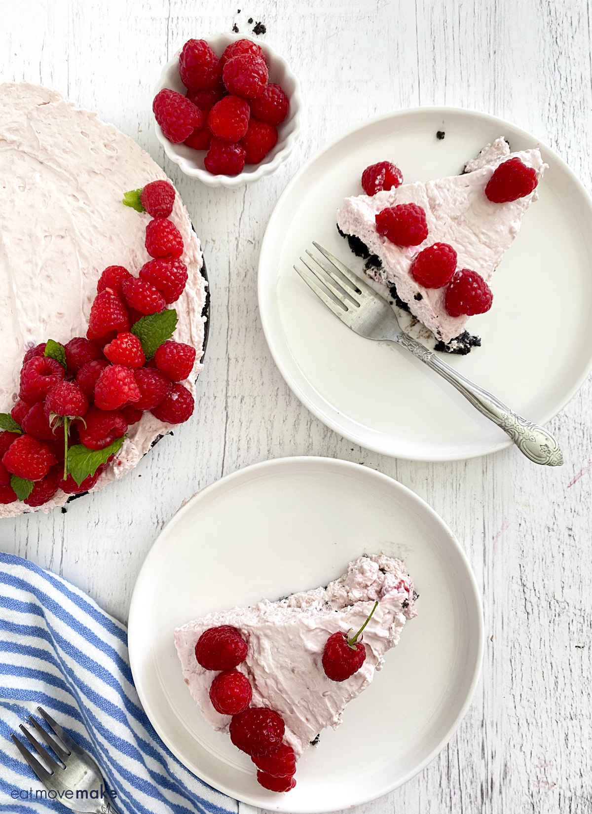 two plates with raspberry pie, bowl of raspberries and whole raspberry no bake cheesecake on white table