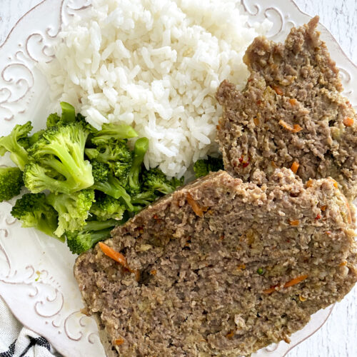 two slices of meatloaf, broccoli and rice on white plate on table next to striped linen