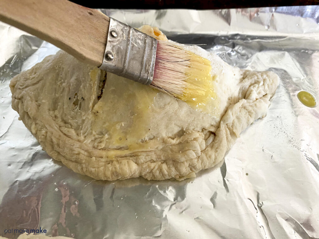 brushing egg wash over top of calzones
