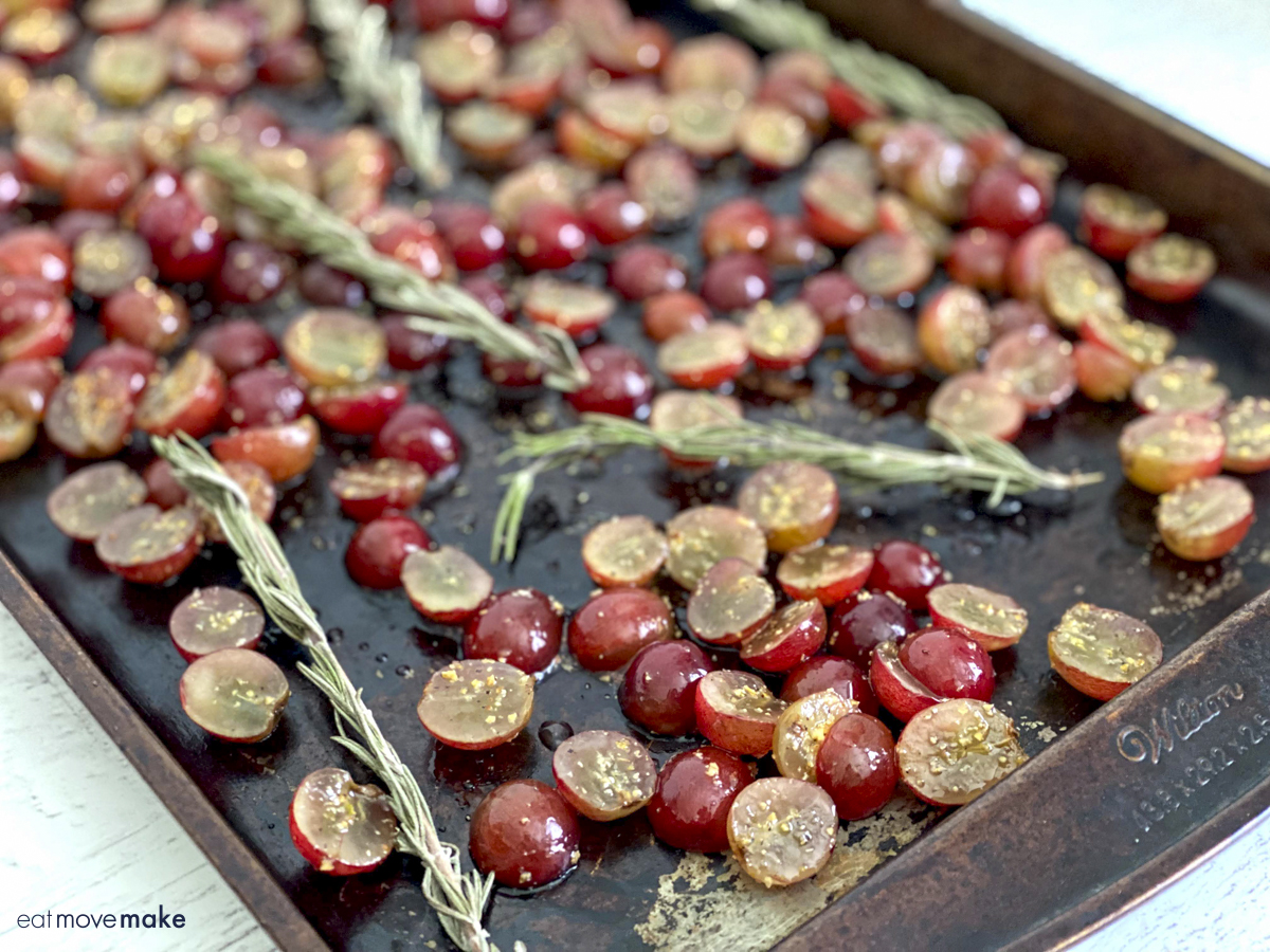 grapes and rosemary sprigs on baking sheet