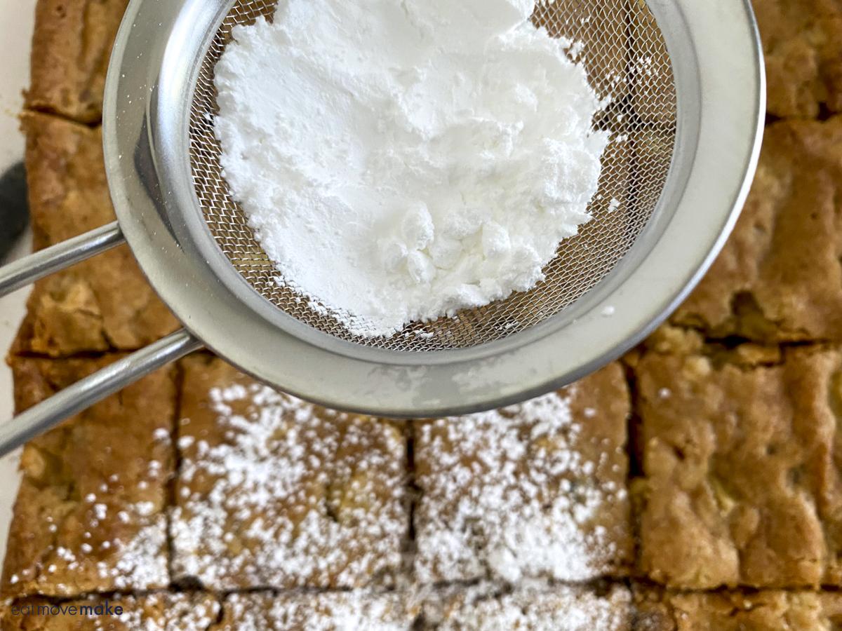 sprinkling powdered sugar on apple brownies