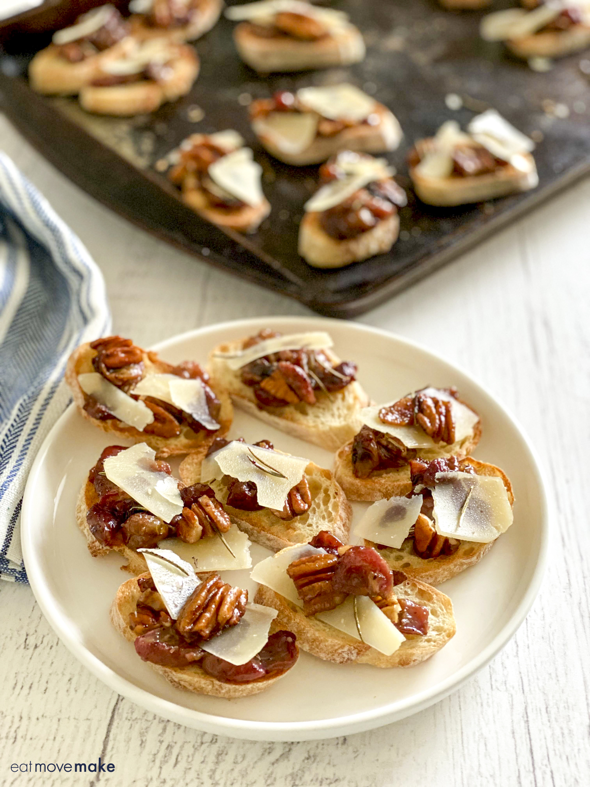white plate of roasted grapes appetizers in front of baking sheet with more crostinis on it