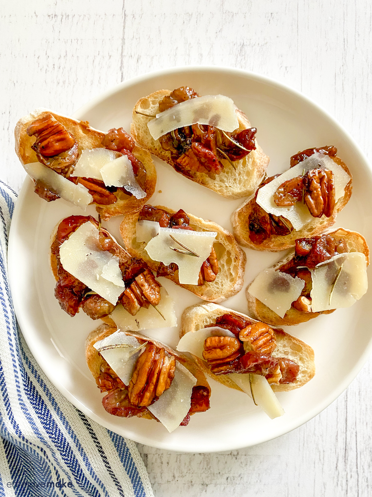 white plate with roasted grapes crostini with rosemary and pecans