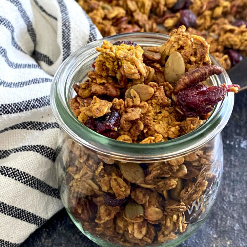 small jar of pumpkin seed granola by striped linen