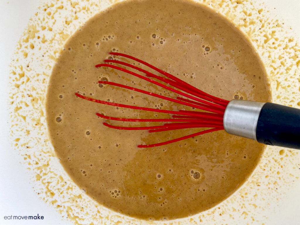 whisk in bowl with pumpkin mixture