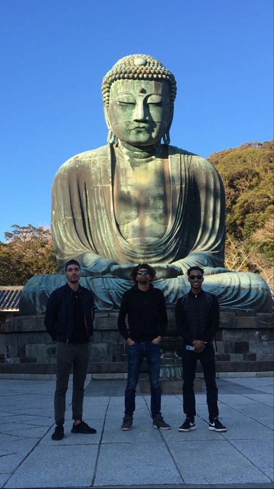 groupe d'amis devant un grand buddha au japon