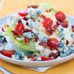 Wedge of iceberg lettuce with blue cheese dressing, sliced cherry tomatoes, bacon crumbles, and blue cheese on a white salad plate