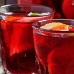 Glasses of fruity red wine sangria garnished with lemon and lime slices