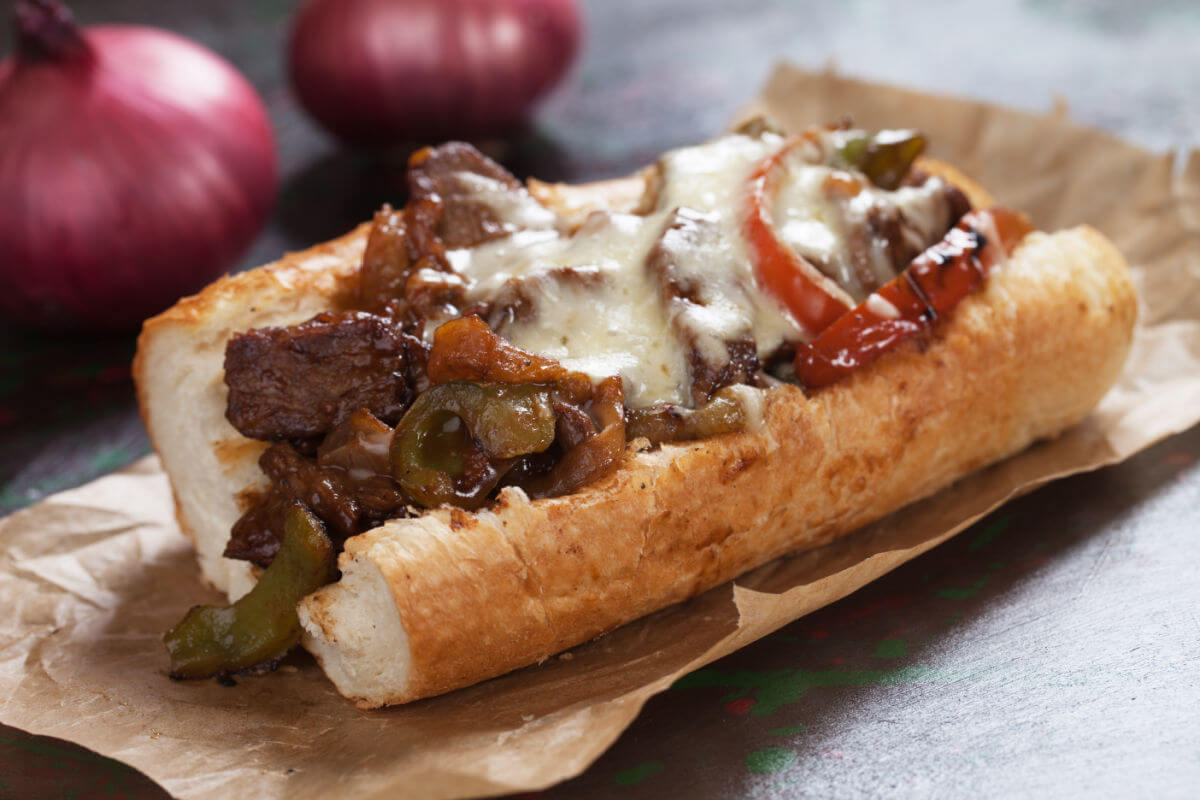 Philly cheesesteak hoagie on brown paper.