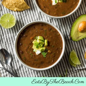 A bowl of Cuban Black Bean Soup garnished with sour cream and avocado