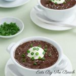 A white crock of savory, spicy Cuban black bean soup flavored with bacon and garnished with sour cream and sliced scallions.