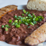 White bowl of creamy and spicy red beans and rice served with a side of grilled Andouille sausage and French bread, garnished with sliced scallions