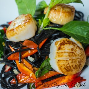 A plate of stir-fried black squid ink pasta, red peppers, carrots and scallops.