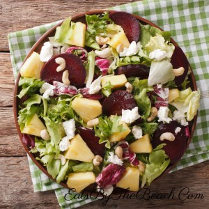 A healthy salad of roasted beets, fresh pineapple, goat cheese, radicchio, romaine lettuce, and cashews. This salad is dressed in a white wine vinaigrette. So light, fresh, and delicious.