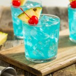 A glass of a Blue Hawaii cocktail - a sweet, fruity summer cocktail, garnished with a pineapple wedge and a Maraschino cherry.