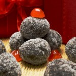 Tray of decadent chocolate bourbon balls coated with superfine sugar and garnished with a maraschino cherry half. A boozy no-bake treat perfect for a Kentucky Derby party or holiday cookie tray.