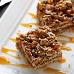 Plate of decadent Gooey Caramel Pecan Pie Bars with a drizzle of caramel sauce and sprinkle of sea salt.