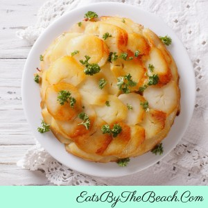 A beautiful plate of Pommes Anna - classic French side dish of sliced potatoes, butter, Parmesan cheese, thyme, and garlic that is browned in a skillet and baked, then inverted onto a serving plate. Sophisticated and simple.