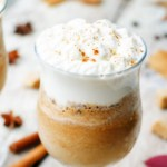 Glass of Iced Pumpkin SPice Latte garnished with whipped cream and a sprinkle of cinnamon.