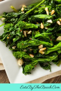 A plate of spicy Italian style broccoli rabe - broccoli rabe sauteed with garlic, red pepper flakes, pine nuts, and Parmesan cheese.