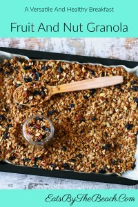 Baking pan of homemade fruit and nut granola - full of oats, pecans, almonds, sunflower kernels, dates, currants, and cinnamon.
