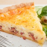 A pie plate of Classic Quiche Lorraine with bacon and Gruyere cheese.