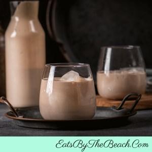 A carafe and 2 glasses of homemade Espresso Irish cream liqueur