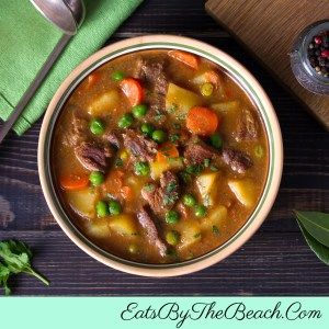 Bowl of savory Irish beef stew - tender beef, onions, potatoes, carrots, and peas in a Guinness and red wine gravy.