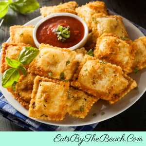 A plate of toasted ravioli - cheese ravioli, breaded and baked and served with marinara sauce.