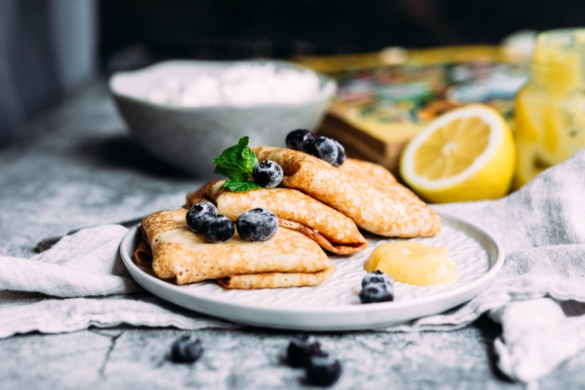 Plate of Lemon Blueberry Bavarian Pancakes garnished with fresh blueberries and lemon curd.