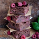 Perfect for St. Patrick's Day, a plate of raspberry Irish stout brownies, fresh raspberries, and a glass of milk stout beer.