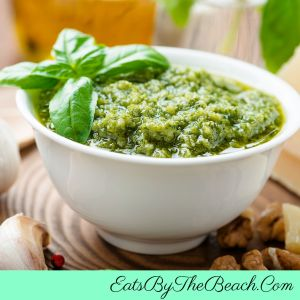 A bowl of fresh pesto sauce with parmesan cheese, lemon juice, spinach, basil, and garlic. Perfect for pasta, on a pizza, drizzled over vegetables, or to top scrambled eggs.