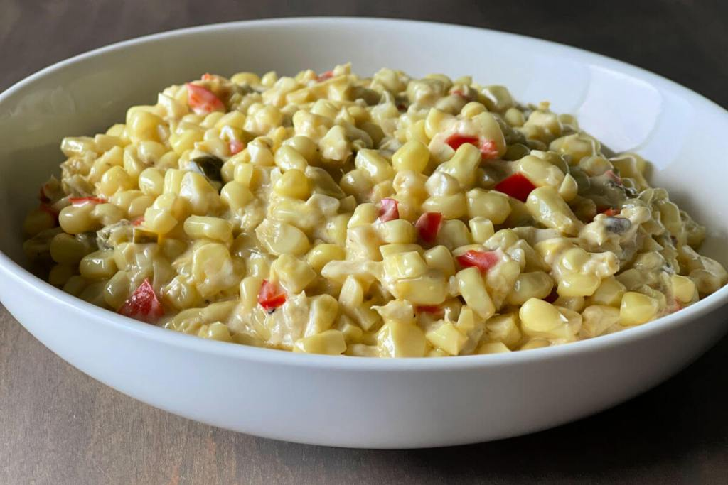 Bowl of green chile creamed corn with fresh corn kernels. jalapenos, canned green chiles in a creamy sauce.