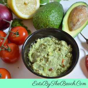 Bowl of The Best Guacamole with onion, lime, jalapenos, and tomatoes. Perfect for CInco De Mayo.