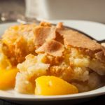 Baking dish with homemade macaron peach cobbler. Fresh peaches are baked in a sweet syrup and a topping that's reminiscent of the famous French cookie.