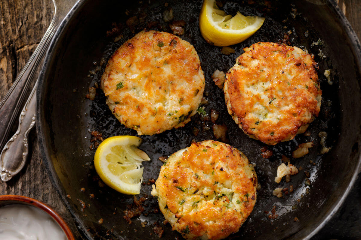 A skillet with 3 Tavern On The Green crab cakes and wedges of lemon