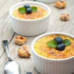 Ramekins of easy creme brulee garnished with blueberries and mint.