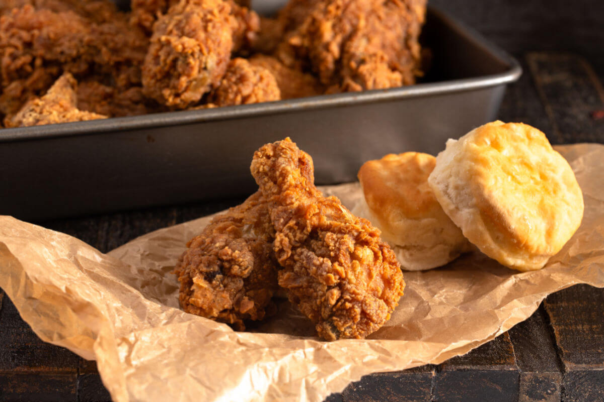 2 drumsticks of extra crispy bourbon fried chicken on a brown paper with biscuits on the side.