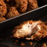 Pan pan of extra crispy bourbon fried chicken with one piece that has a bite taken out of it