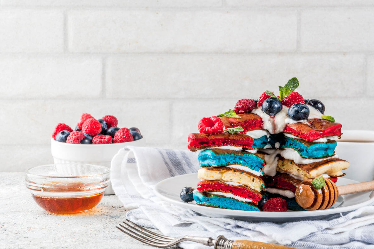 A plate of Patriotic Pancakes - red, white, and blue pancakes topped with French Chantilly Cream, blueberries, raspberries, and a sprig of fresh mint.