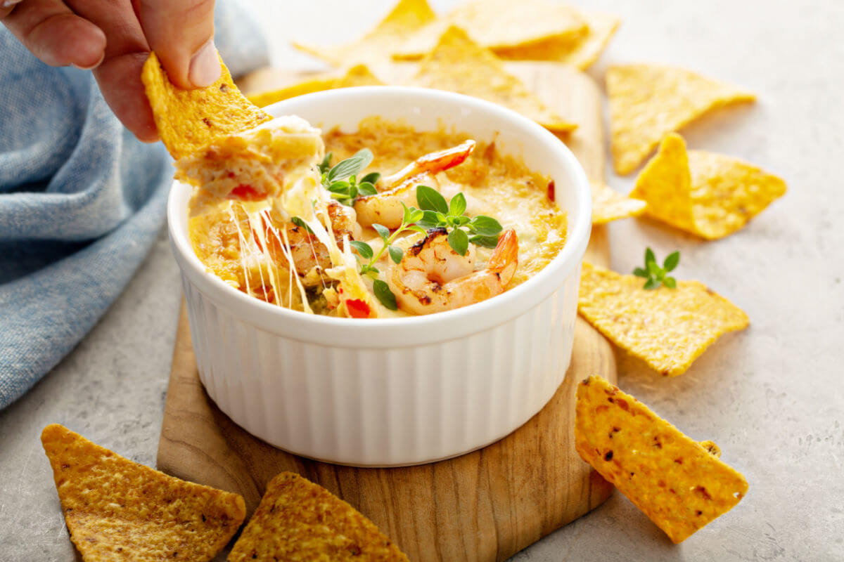 Ramekin of Spicy Seafood Dip garnished with poached shrimp and fresh thyme and served with tortilla chips.