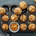 Muffin pan with bakery-style almond muffins topped with sliced almonds and an amaretto syrup glaze.