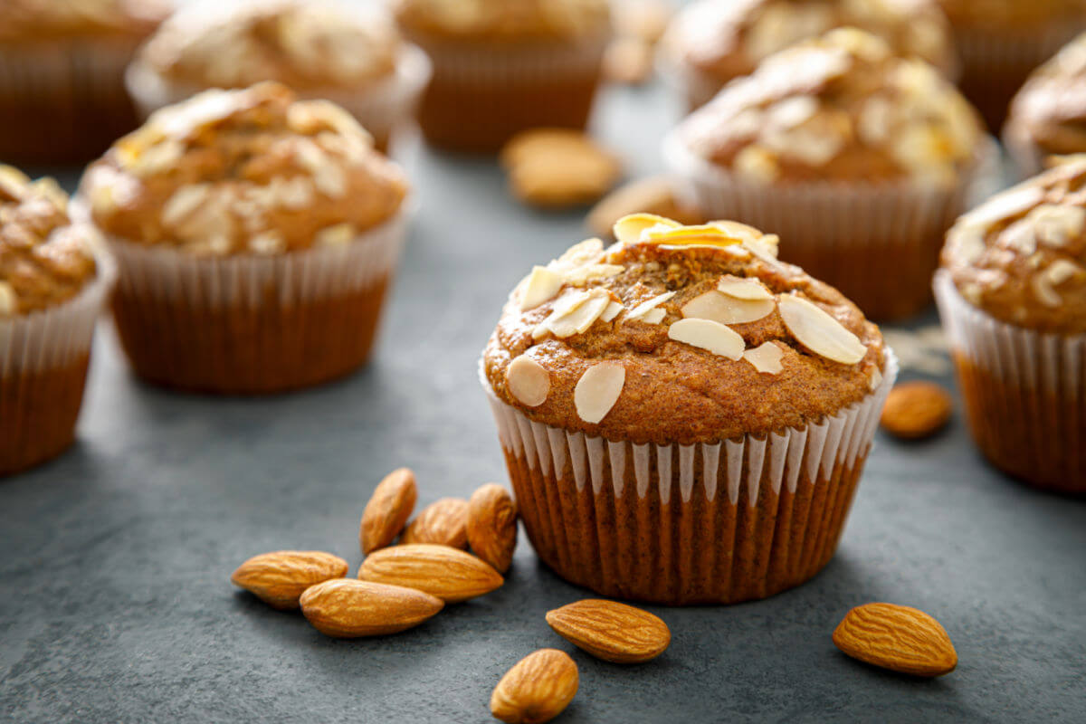 Closeup of a bakery-style almond muffin with sliced almonds and amaretto glaze on top.