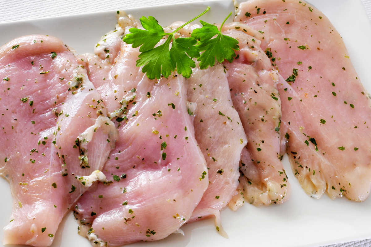 Plate of marinated raw chicken breasts for flavorful chicken fajitas.
