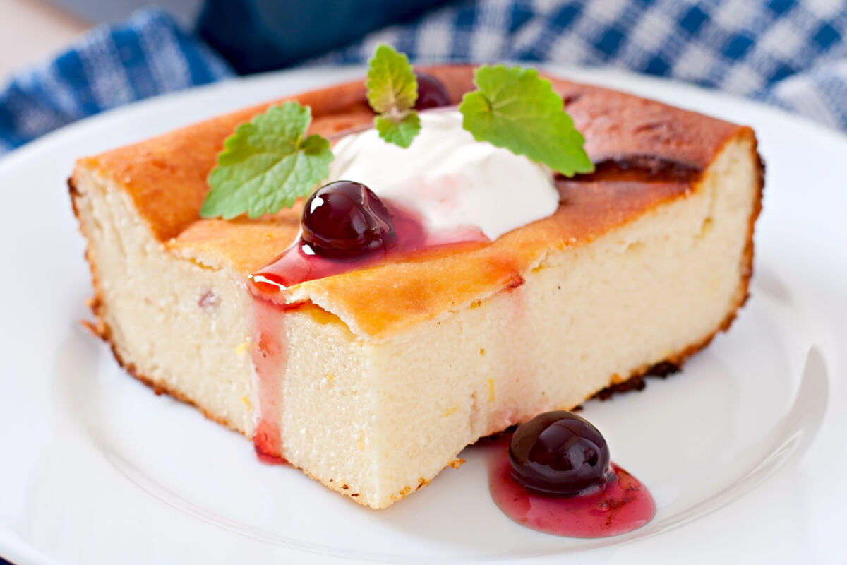 A square of Russian Breakfast Cheesecake garnished with sour cream, blueberries in syrup, and mint sprigs.