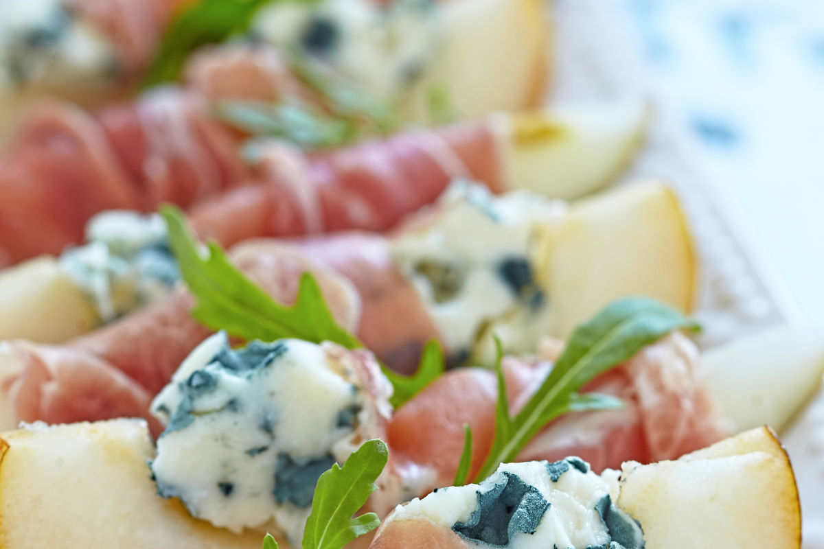 Platter of prosciutto wrapped pears stuffed with blue cheese and arugula.