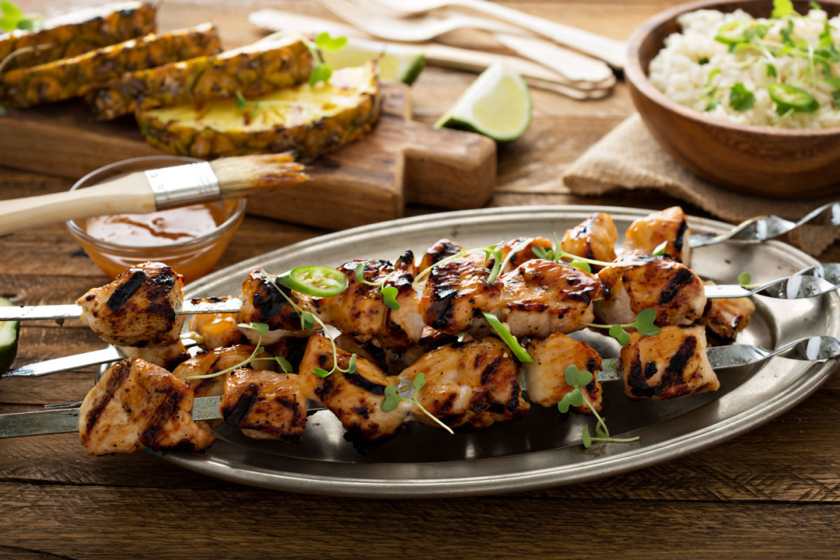 Pewter platter with spicy sweet chicekn kabobs, garnished with persulane and jalapeno.