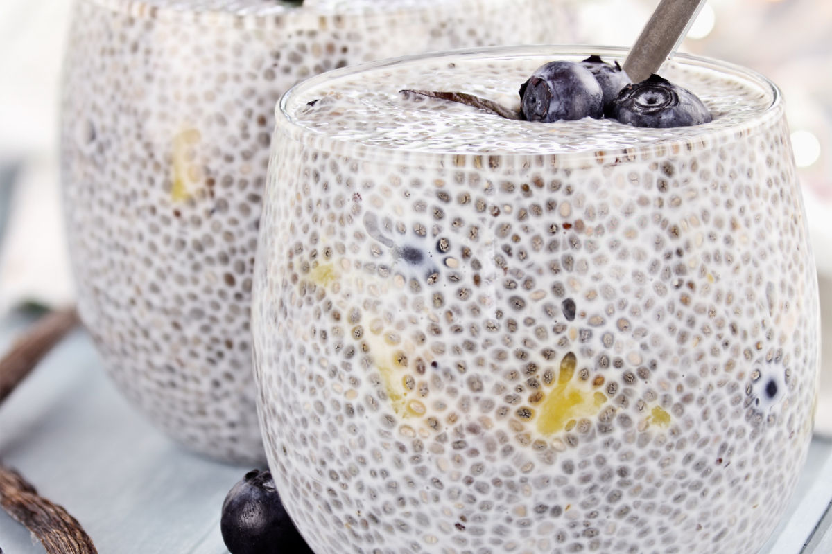 Short glass full of vanilla blueberry chia seed breakfast pudding, garnished with fresh blueberries.