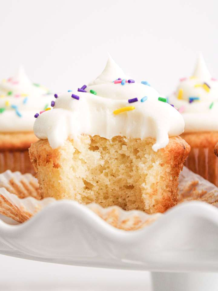 easy vanilla cupcakes on cake stand with bite missing
